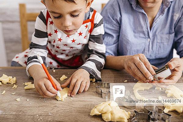 Junge schneidet Kekse mit Werkzeug aus