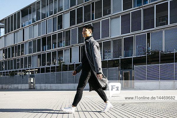 Spanien  Barcelona  lächelnder junger Mann geht die Straße entlang