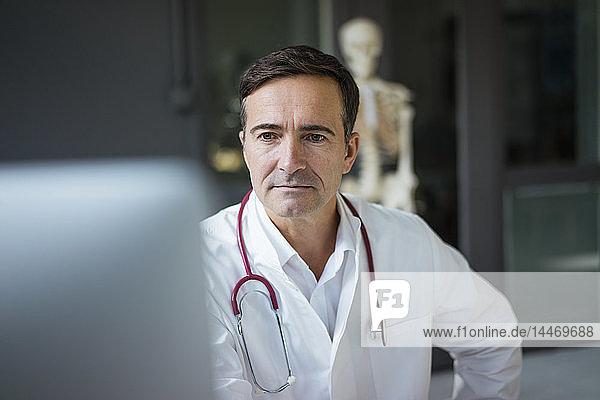 Arzt in medizinischer Praxis betrachtet Computer mit Skelett im Hintergrund