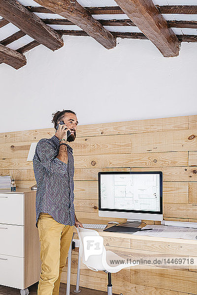 Young architect in office at home talking on the phone