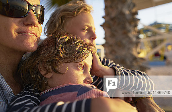 Mother with two sons on the beach at sunset