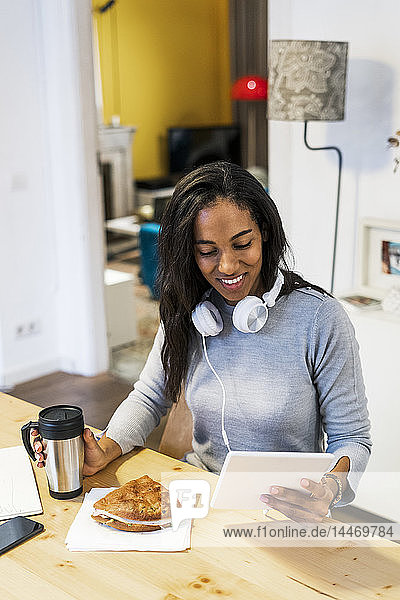 Smiling woman using tablet at table