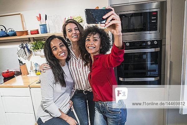 Three happy women posing for a selfie in kitchen