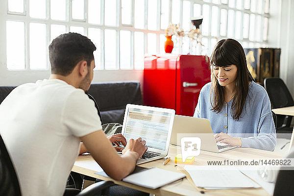 Kollegen mit Laptops am Schreibtisch im Büro