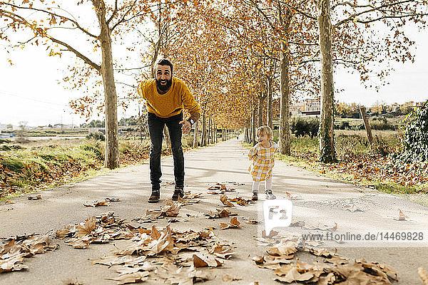 Vater und Tochter spielen im Herbst auf einem Weg im Park