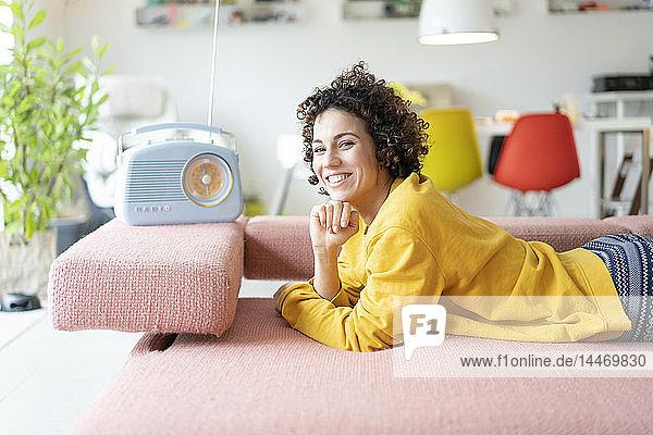 Porträt einer glücklichen Frau  die auf einer Couch liegt und zu Hause mit einem tragbaren Radio Musik hört