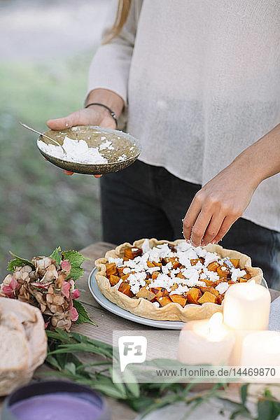 Nahaufnahme einer Frau  die im Freien ein romantisches Essen bei Kerzenlicht zubereitet