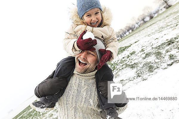 Playful father carrying daughter piggyback in winter landscape