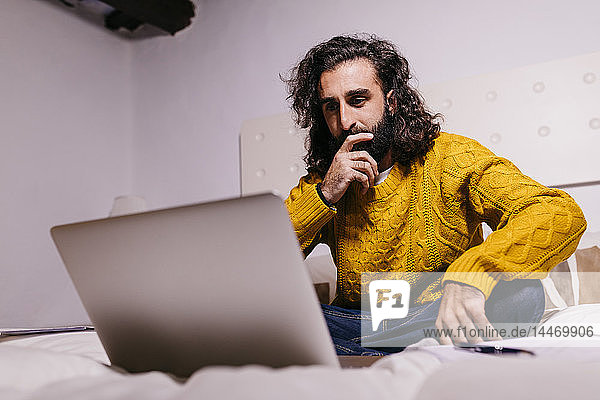 Young man using laptop in bed at home