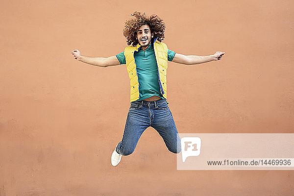 Porträt eines lächelnden jungen Mannes mit lockigem Haar und gelber Weste  der in die Luft springt