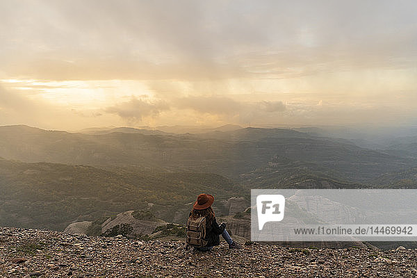 Woman with backback  sitting on mountain  looking at view