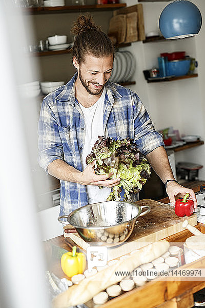 Young man preparing food at home  cleaning lettuce