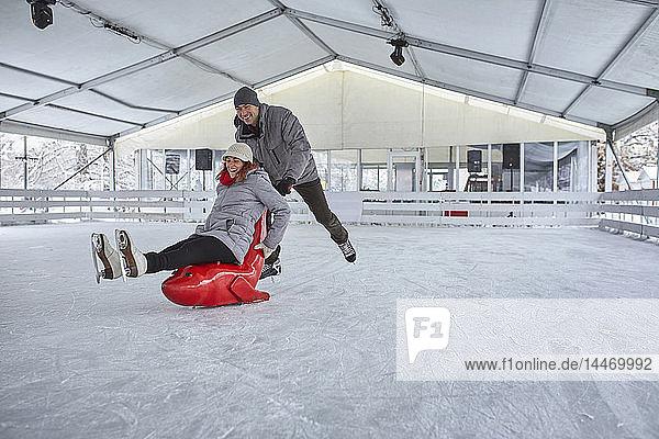 Eislaufen zu zweit  mit Robbenschlitten zum Schieben der Frau
