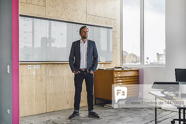 Geschäftsmann steht in seinem Büro vor dem Whiteboard  die Hände in den Taschen