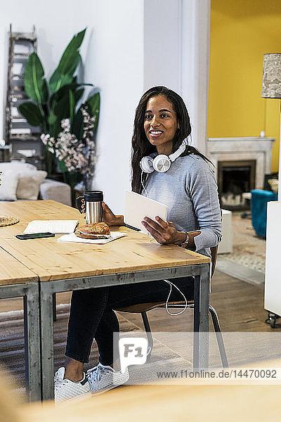 Lächelnde Frau mit Tablette am Tisch sitzend