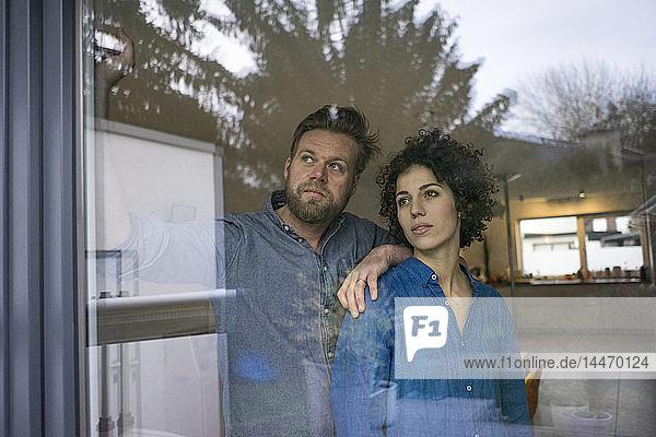 Ernsthaftes Ehepaar zu Hause hinter dem Fenster und schaut hinaus