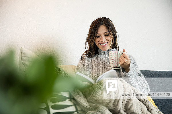 Woman sitting on couch  wrapped in a blanket  reading book  drinking tea