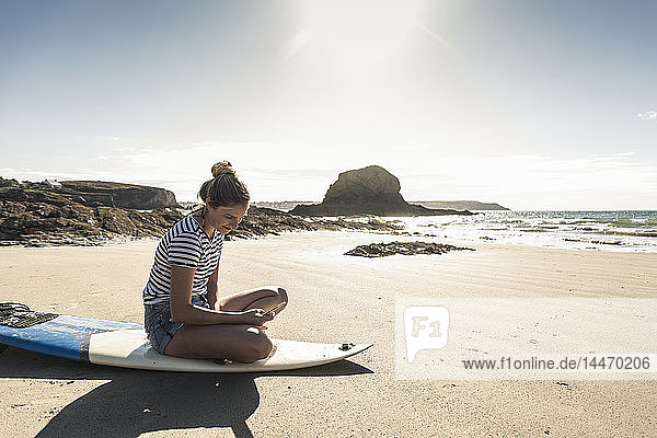 Young woman on the beach  sitting on surfboard  using smartphone