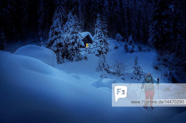 Österreich  Bundesland Salzburg  Schneeschuhwandern  Frau nachts in der Nähe der Hütte