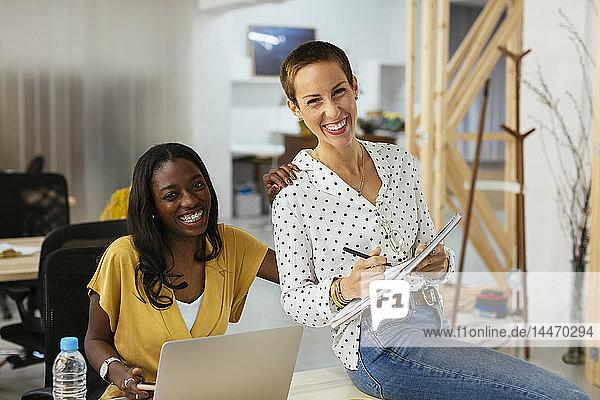 Porträt von zwei glücklichen Kollegen am Schreibtisch im Büro