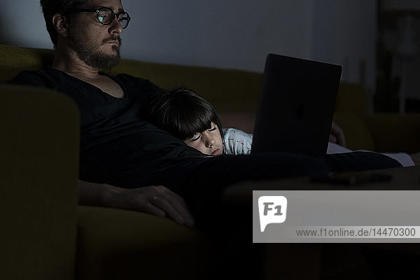 Father using laptop on couch at night with daughter sleeping