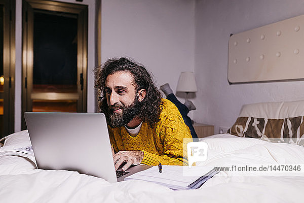Smiling young man lying in bed at home using laptop