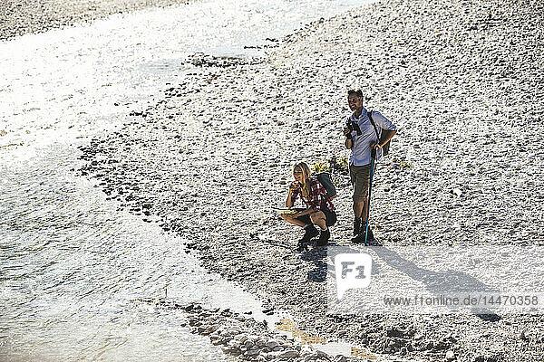 Österreich  Alpen  Paar auf Wanderung mit Rast an einem Bach