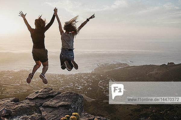 Südafrika  Kapstadt  Kloof Nek  zwei Frauen springen bei Sonnenuntergang auf Felsen