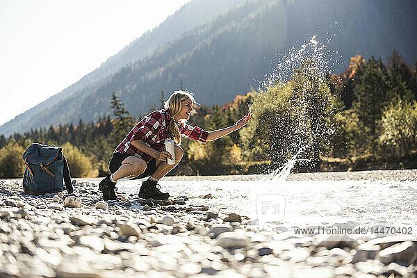 Österreich  Alpen  Frau auf Wanderung  die an einem Bach mit Wasser spritzt