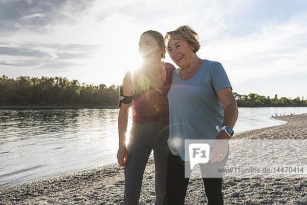 Fitte Großmutter und Enkelin  die mit den Armen am Fluss spazieren gehen und Spaß haben