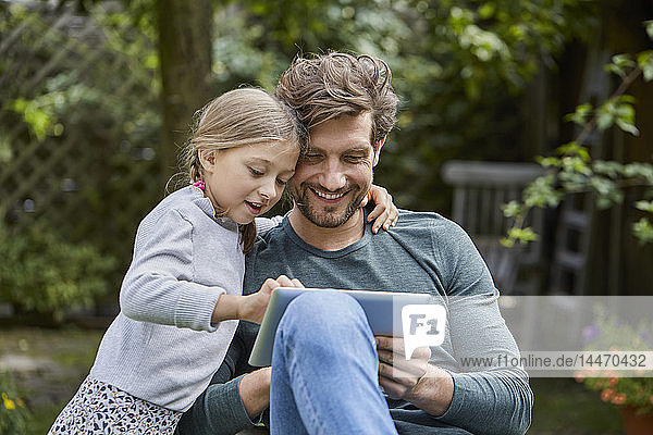 Happy father and daughter using tablet together in garden