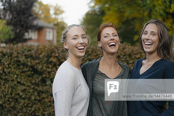 Porträt einer glücklichen Mutter mit zwei Teenager-Mädchen im Garten