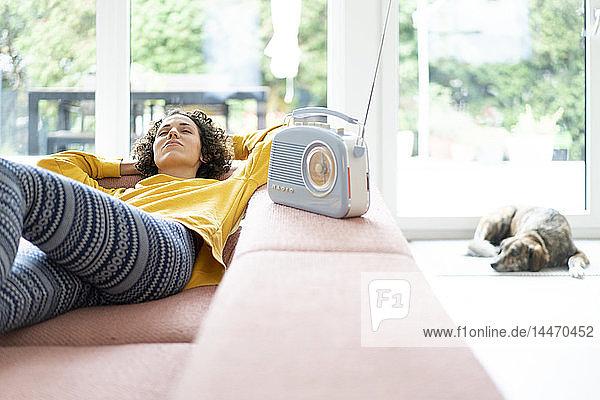 Frau liegt auf dem Sofa und hört zu Hause Musik mit einem tragbaren Radio
