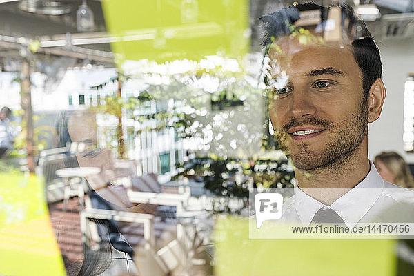 Geschäftsmann mit Kollege beim Brainstorming mit Post-its an der Fensterfront