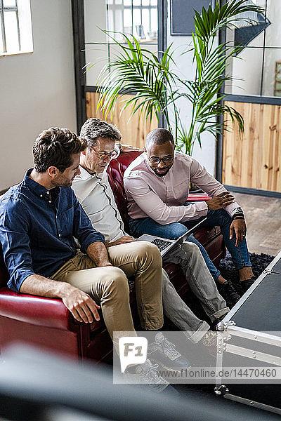 Drei Geschäftsleute sitzen mit Laptop auf dem Sofa im Loft-Büro