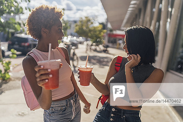 USA  Florida  Miami Beach  two carefree female friends having a soft drink in the city