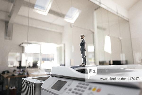 Businessman figurine standing on copy machines in modern office