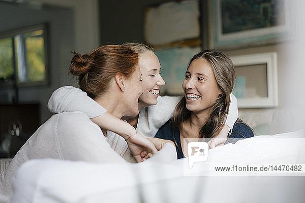 Glückliches Teenager-Mädchen umarmt Mutter und Schwester zu Hause auf der Couch