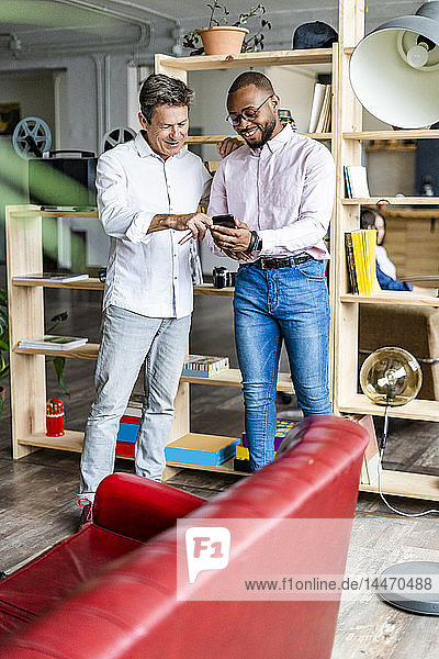 Two smiling businessmen using cell phone in loft office