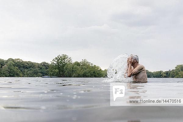Älterer Mann in einem See  der ihm Wasser ins Gesicht spritzt