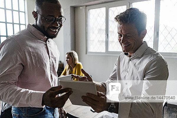Two smiling businessmen with tablets having a meeting in loft office