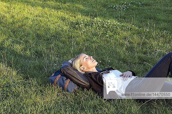 Frau liegt auf einer Wiese in einem Park und entspannt