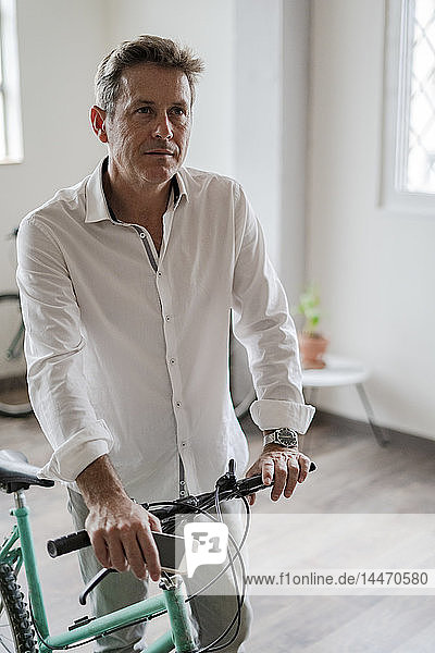 Portrait of businessman with bicycle in office