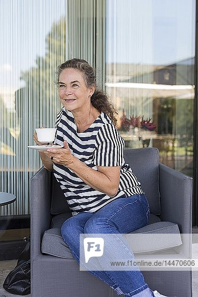 Portrait of smiling mature woman with cup of coffee sitting on lounge chair outdoors