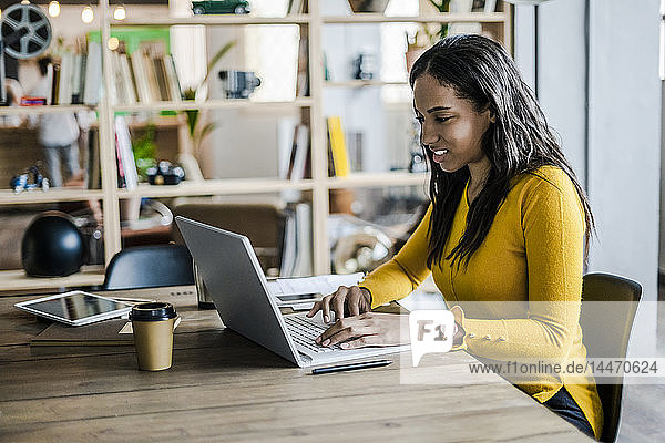 Young businesswoman using laptop at desk in loft office