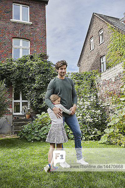 Smiling father with daughter standing in garden of their home