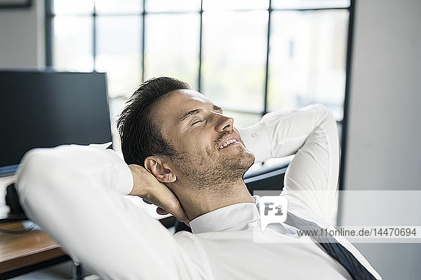 Smiling businessman in office leaning back