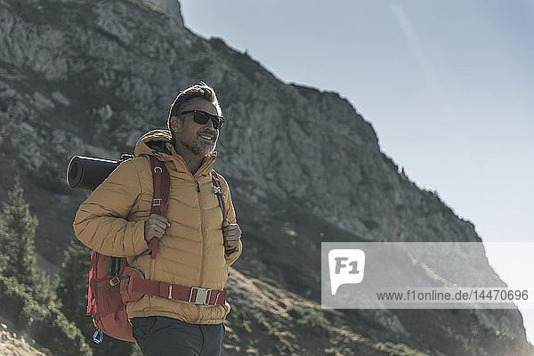 Österreich  Tirol  lächelnder Mann mit Sonnenbrille wandert in den Bergen
