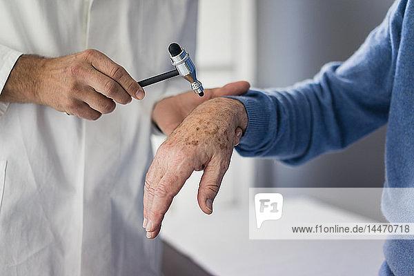 Nahaufnahme eines Arztes  der einen älteren Patienten in der medizinischen Praxis untersucht
