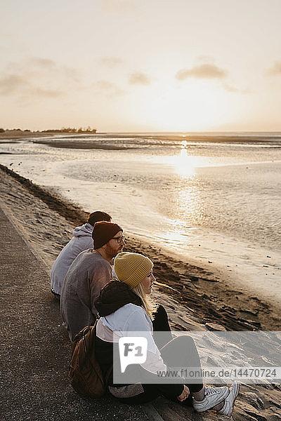 Namibia  Walvis Bay  drei Freunde entspannen sich bei Sonnenuntergang